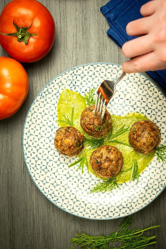 Mediterranean meatballs on a plate with pesto, tomatoes and blue cloth napkin on the side, grey wood background. A hand with a fork in one of the meatballs.