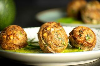 Mediterranean meatballs on a plate with pesto.