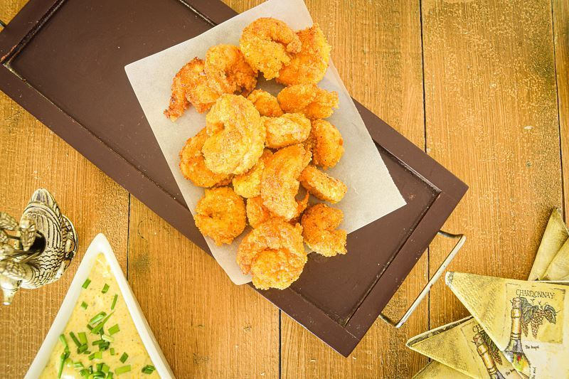 Fried coconut shrimp on a black serving tray, curry dip on the side.