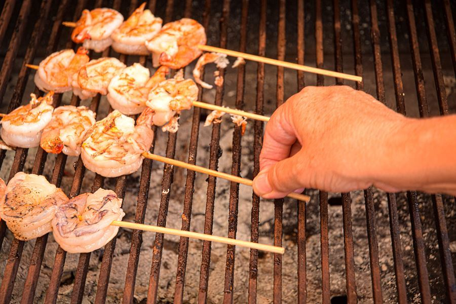 Woman's hand turning shrimp skewers on outdoor grill.
