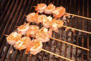 Cooked jumbo shrimp skewers on bbq.
