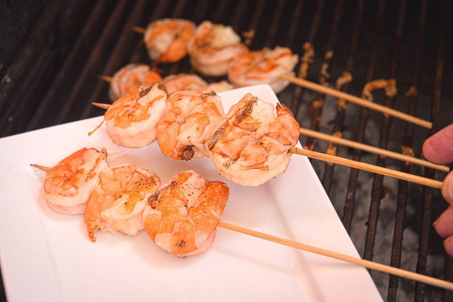 Grilled shrimp skewers on white plate.