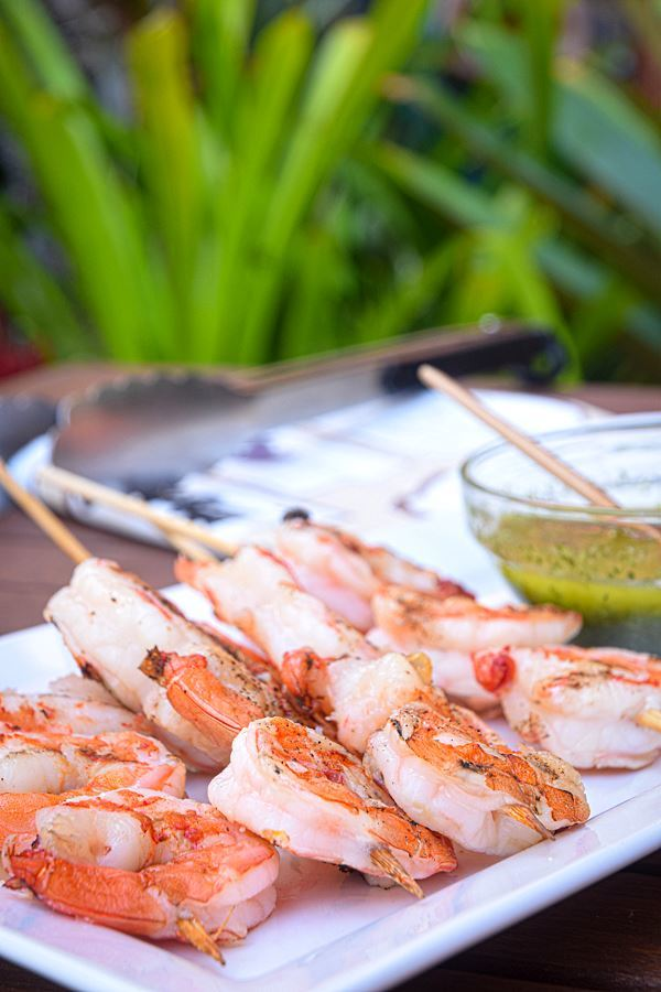 Grilled shrimp skewers on white plate with a bowl of chimichurri sauce.