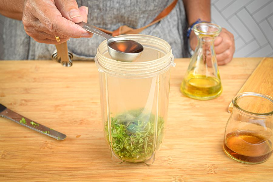 Red wine vinegar pouring into blender jar.