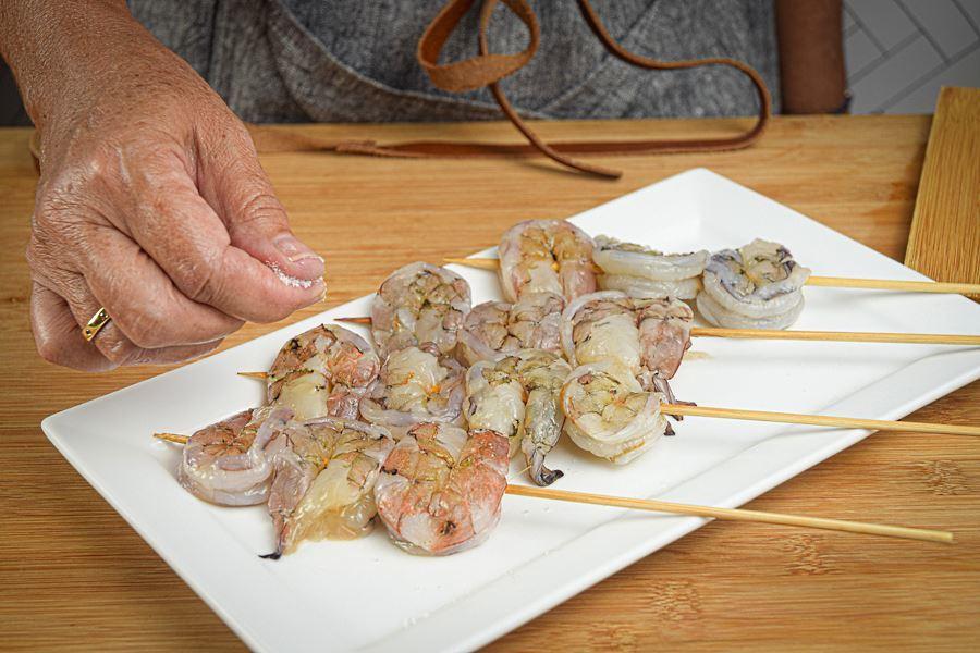 Woman's hand sprinkling salt on shrimp skewers.