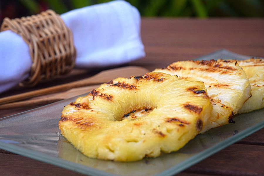 Grilled pineapple slices on a glass serving plate.