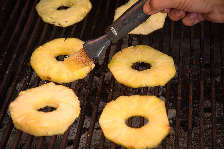 Pineapple slices on the grill, hand brushing them with pastry brush.