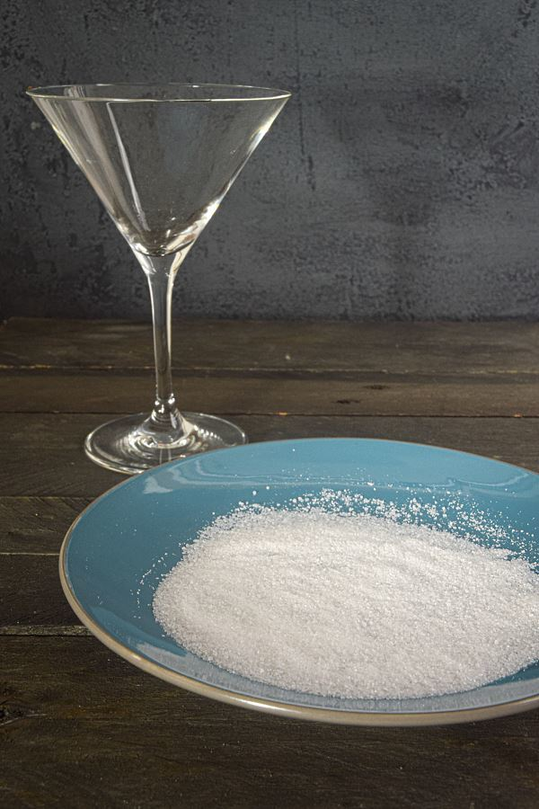 A martini glass and a blue plate with sugar on it.