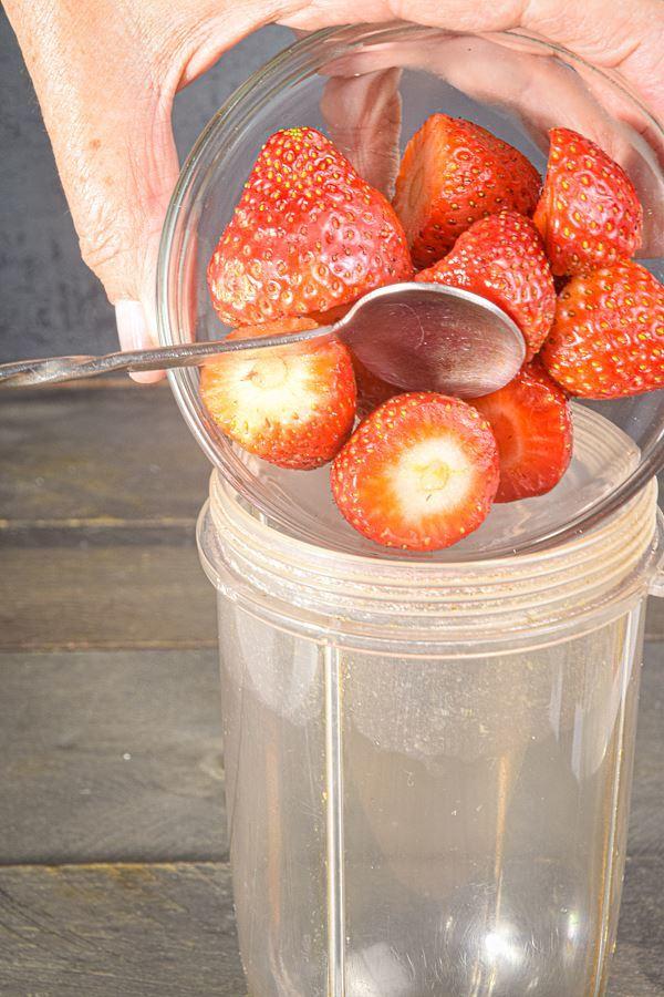 Strawberries being spooned into a blender jar.