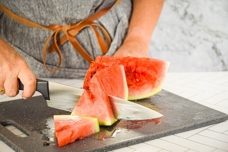 A woman slicing a watermelon into wedges.