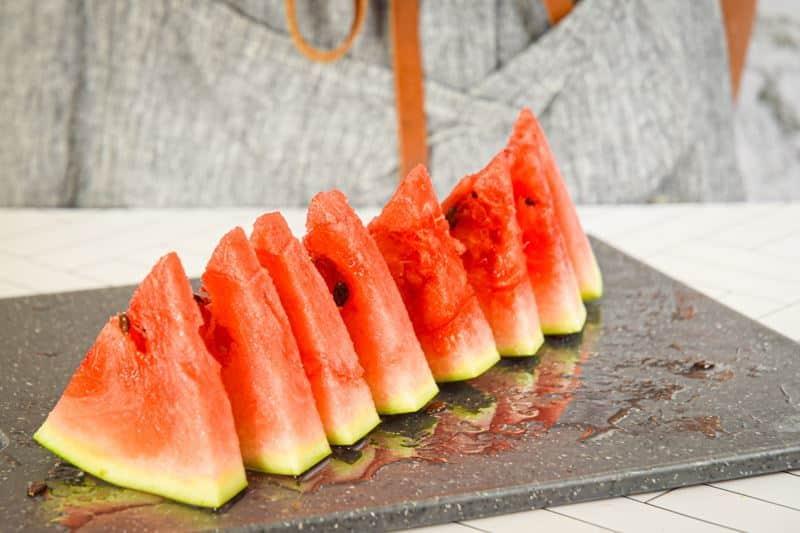 Watermelon triangles on a cutting board.