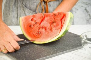 A woman using a knife to peel the rind off the watermelon.