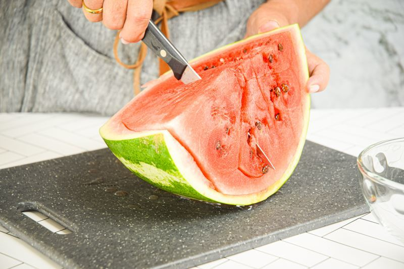 A woman making vertical slices into a watermelon.