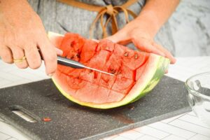 A woman making horizontal slices into a watermelon.