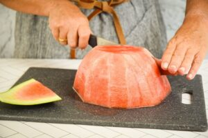 A woman slicing sticks out of a watermelon.