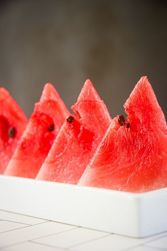 Triangle watermelon slices on a white serving dish.