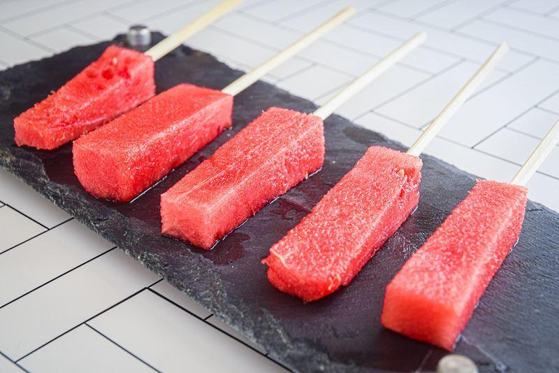 Watermelon sticks on wooden sticks.