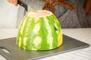 A woman quartering a large watermelon on a cutting board.