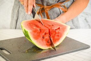 A woman slicing a large watermelon into eighths.