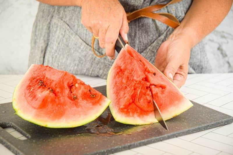 A woman slicing a watermelon.
