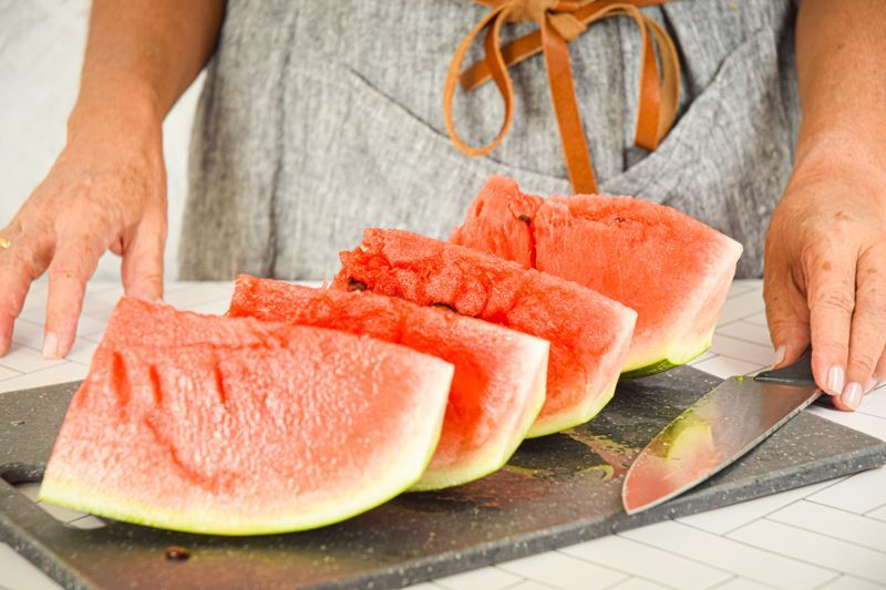 4 large pieces of watermelon on a cutting board.