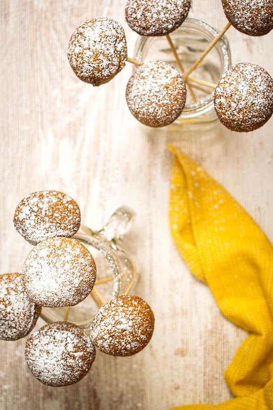 Cake Pop Maker Pumpkin Cake Pops in jars on white background, yellow cloth napkin.
