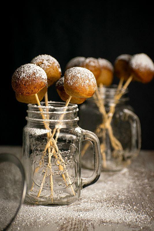 Cake Pop Maker Pumpkin Cake Pops in jar, black background.