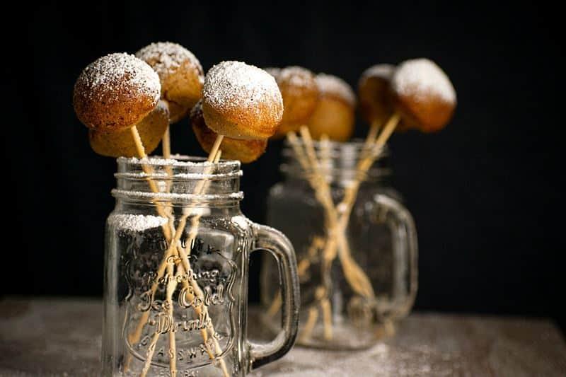 Cake Pop Maker Pumpkin Cake Pops in jars, black background.