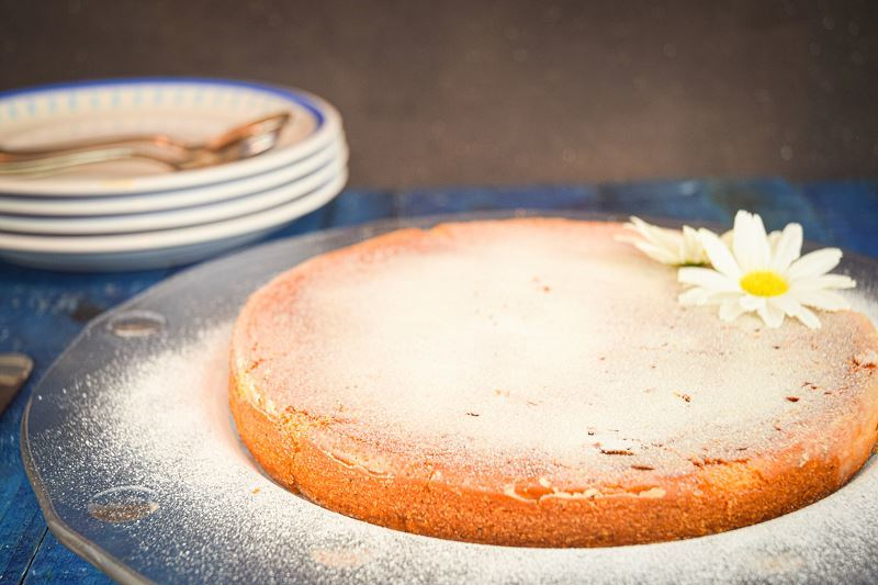 Electric Skillet Yogurt Cake dusted in icing sugar, 2 white flowers on top on a clear plate, blue wooden background.