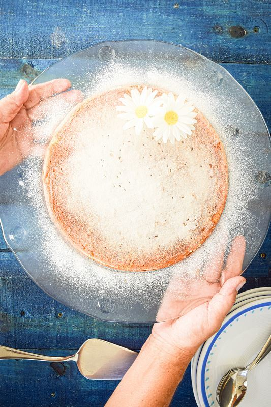 A woman's hand holding a clear plate with electric skillet yogurt cake on it, dusted in icing sugar, 2 white flowers on top, blue wooden background.