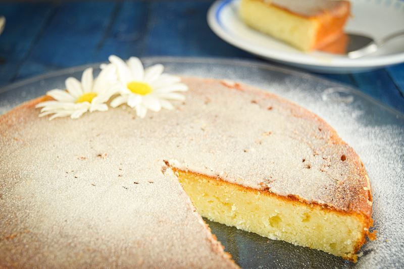 Electric Skillet Yogurt Cake, 1 piece cut out, dusted in icing sugar, 2 white flowers on top on a clear plate, blue wooden background.