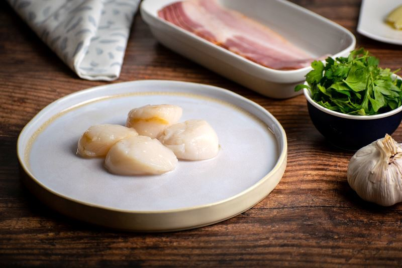 Fresh scallops on a plate, bacon on a plate, garlic and greens in the background.