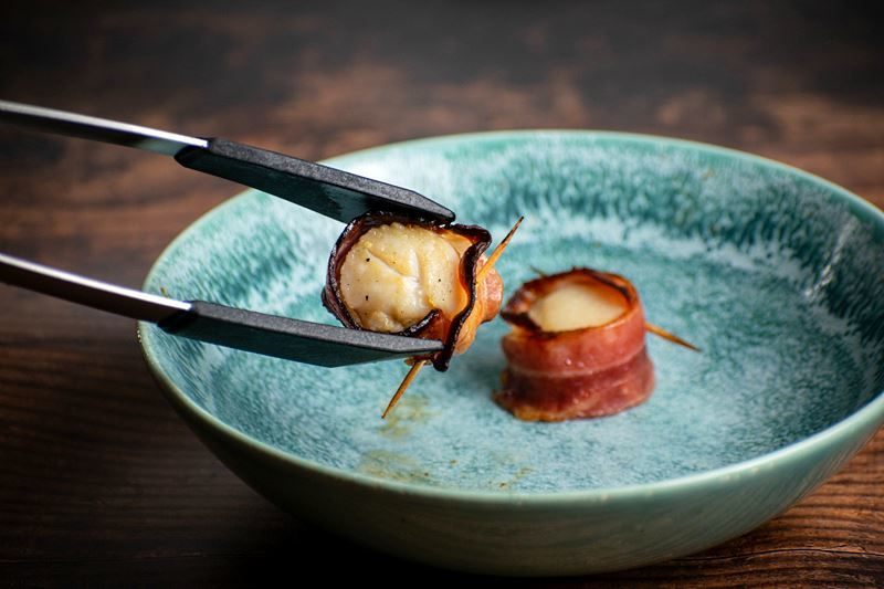 Cooked bacon-wrapped scallops on a blue plate.