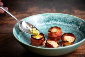 Cooked bacon-wrapped scallops on a blue plate with garlic butter.