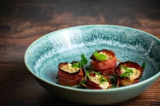 Cooked bacon-wrapped scallops on a blue plate with garlic butter and parsley.