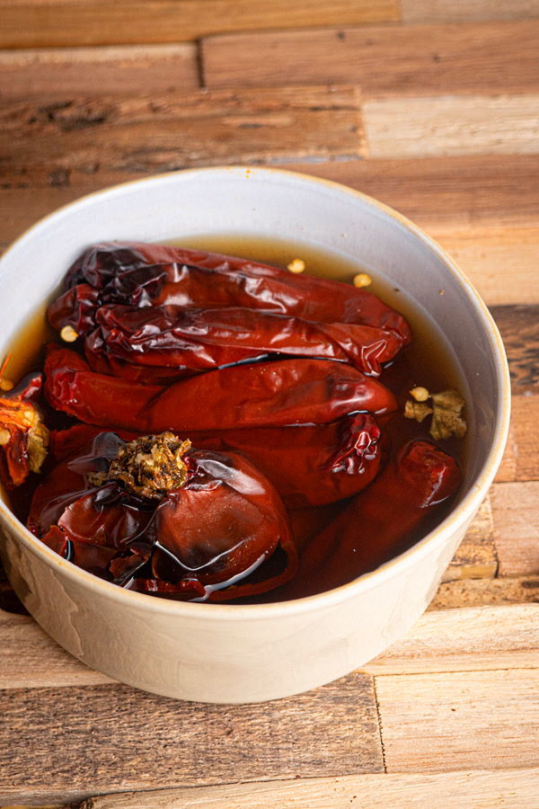 Peppers sitting in a bowl of warm water on wooden background.