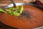 Mole sauce in a bowl with cilantro and black sesame seed toppings, wooden background, dried peppers in the background.