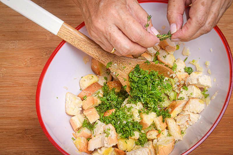 Stuffing in a bowl, thyme being added to mix, wooden spoon.