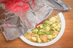 Stuffing in a bowl, foil over top, wooden background.