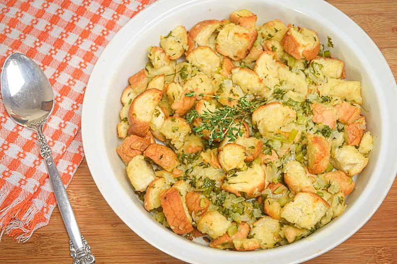 Stuffing mix on a plate with a spoon, wooden background.