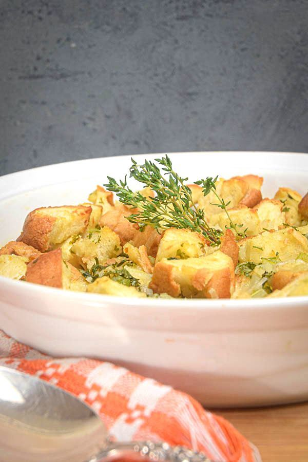 Stuffing mix on a plate with a spoon, dark background.