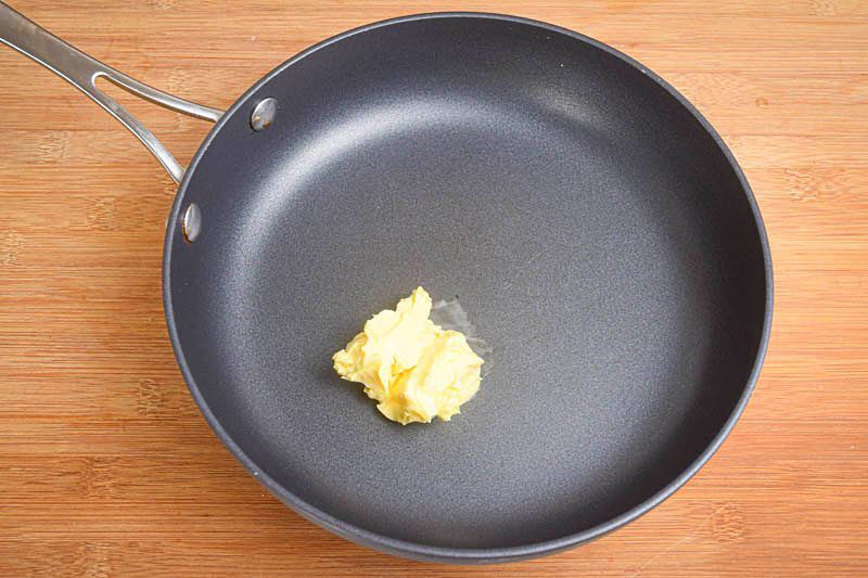 Butter in a frying pan, wooden background.