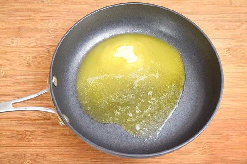 Butter in a pan, wooden background.