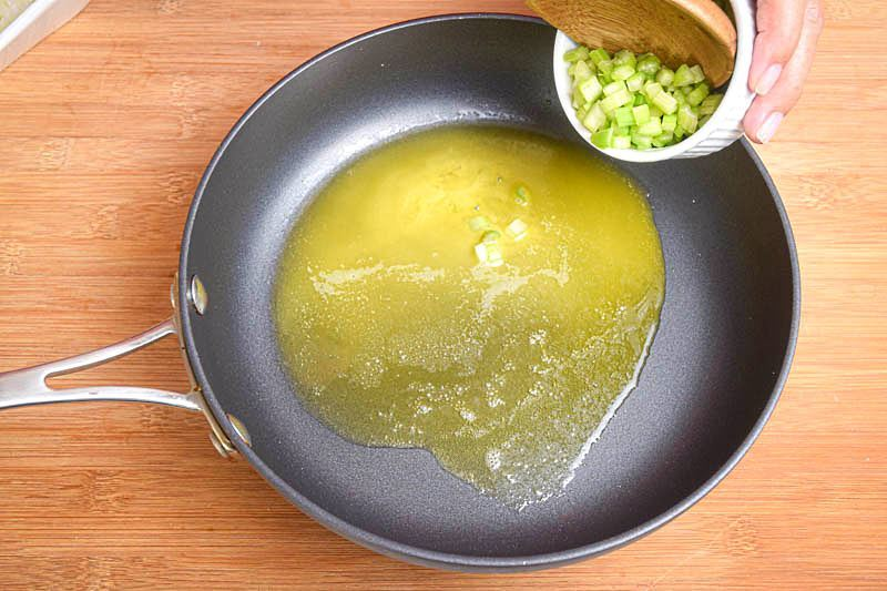 Butter and onions in a pan, wooden background.