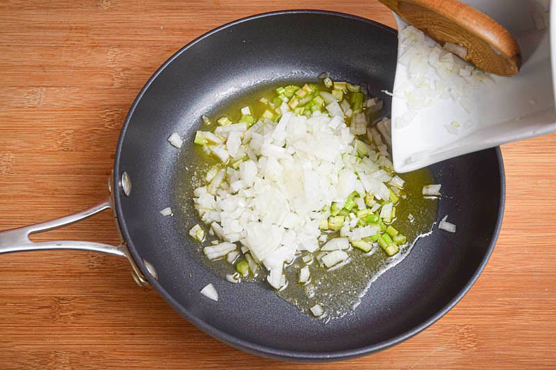 Onions and butter in a pan, wooden background.