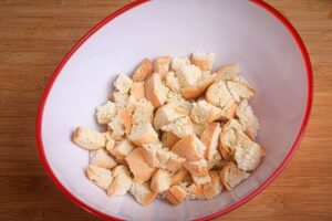 Cubed bread in a bowl, wooden background.