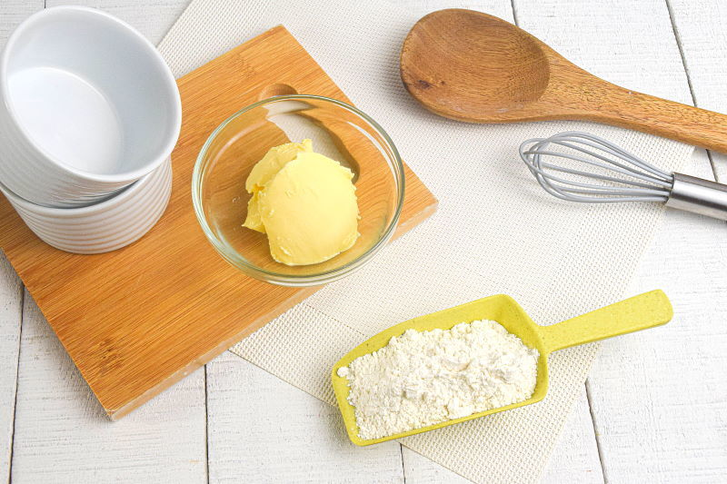 Roux ingredients on a cutting board: butter and flour.