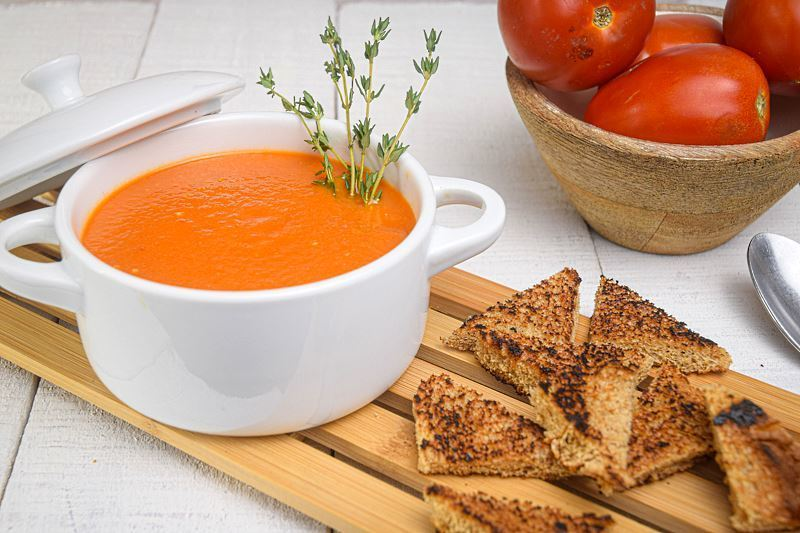 Roasted Tomato Soup in a white porcelain soup bowl with thyme sprigs, toasted bread on the side, bowl of tomatoes in the background.