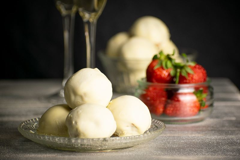 Strawberry Champagne Cake Balls on a clear dish, black background. Glasses of champagne in the background and strawberries.