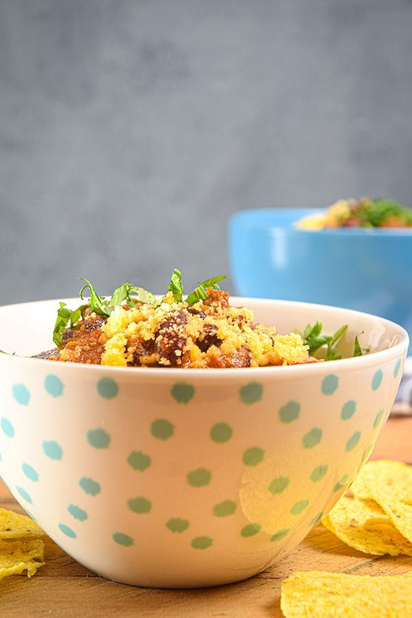 Electric Skillet Chili in a white bowl with blue polka dots, tortilla chips on the side.